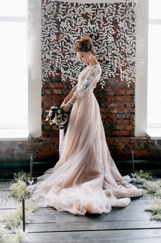 a beautiful wedding dress with a white lace applique bodice, long sleeves and a layered blush skirt