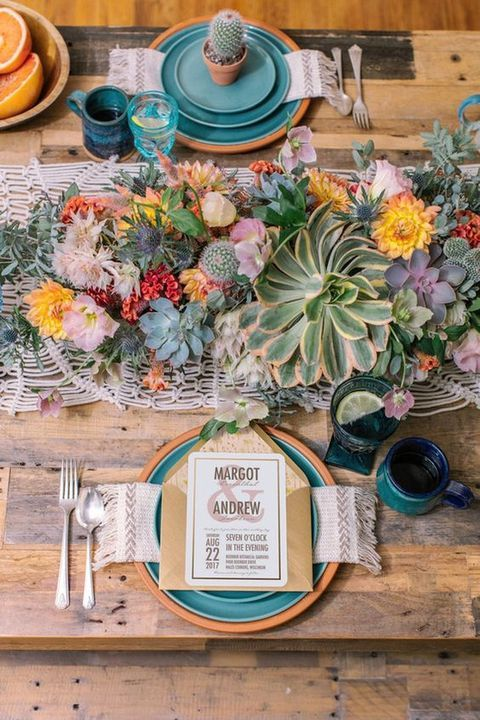 a colorful table setting with a crochet table runner, lush blooms, succulents and cacti plus turquoise touches
