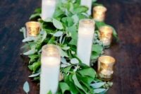 02 a fresh eucalyptus table runner with cathedral candles is a great idea for a spring wedding