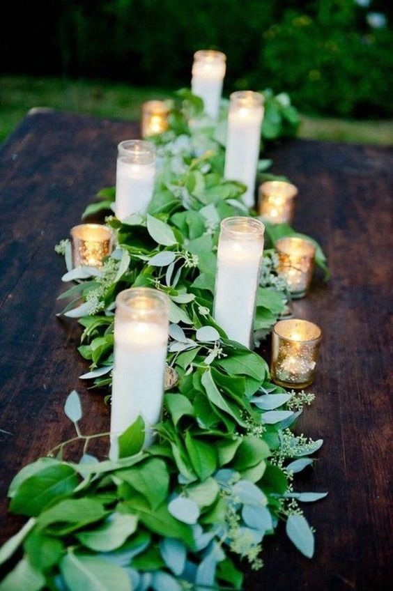 a fresh eucalyptus table runner with cathedral candles is a great idea for a spring wedding