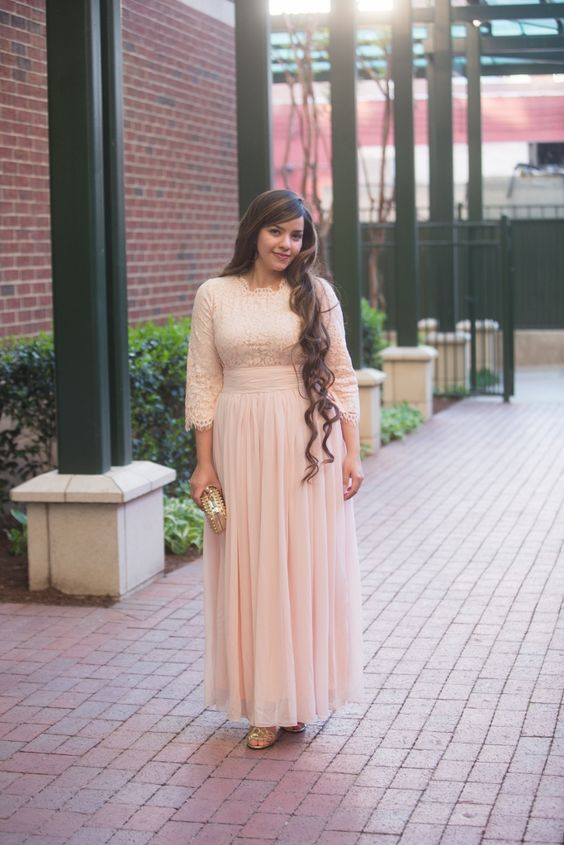 a modest blush bridesmaid's dress with a lace bodice and long sleeves and a maxi skirt