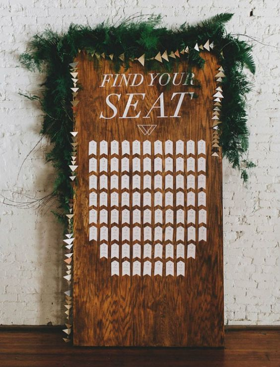 a wooden board with a geometric seating chart, a geo banner and a lush greenery garland on top