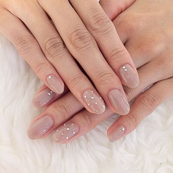 nude nails with tiny rhinestones and a whole accent rhinestone nail for a glitter touch