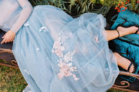 03 The bride was earing a light blue wedding gown with a sheer bodice, long sleeves and a train, with tender pink floral appliques