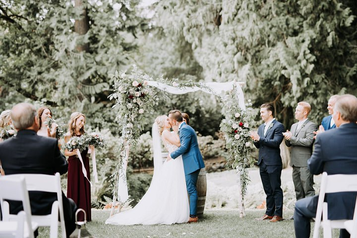 The wedding ceremony space was done with a lush greenery and bloom arch and airy fabric