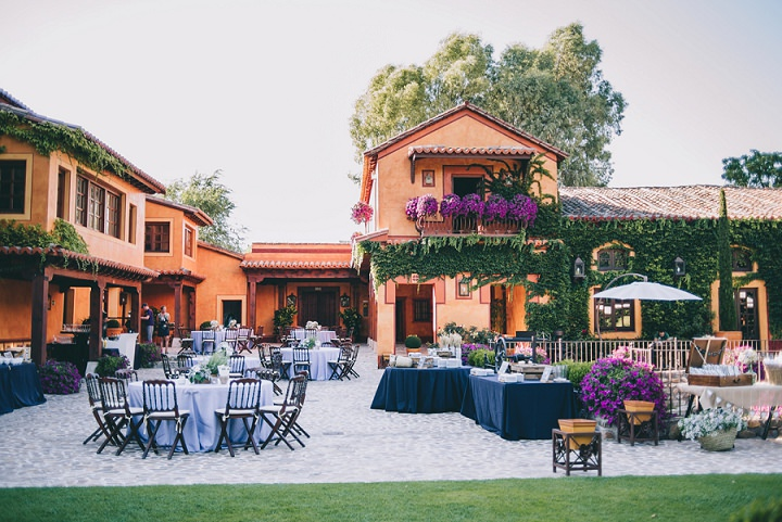 The wedding reception space was done with lush greenery and fuchsia flowers, with tables with tablecloths of lavender and navy shade