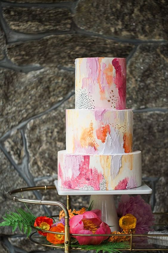 a bold watercolor wedding cake with pink, orange and blue touches for a colorful wedding