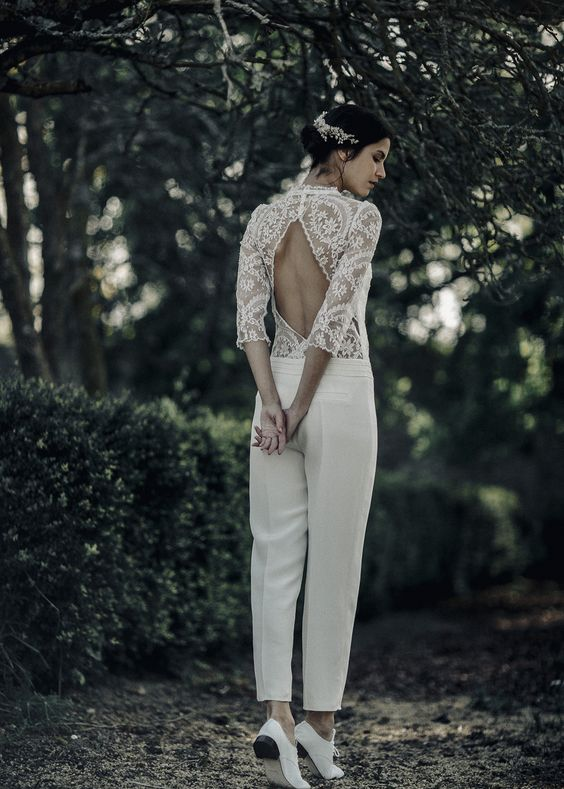 a bridal jumpsuit with plain pants, a lace bodice with long sleeves and a cutout back plus white shoes for a boho feel