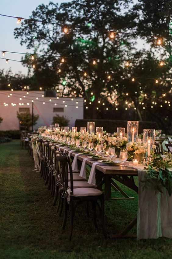 a cozy night garden wedding reception space with candles, greenery and string lights over it