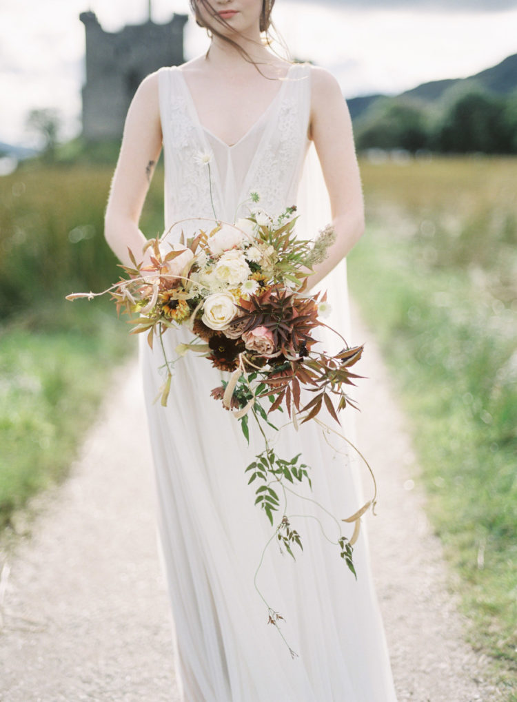 a delicate vintage-inspired wedding dress with thick straps, a lace bodice, a V-neckline and a flowy skirt with a train
