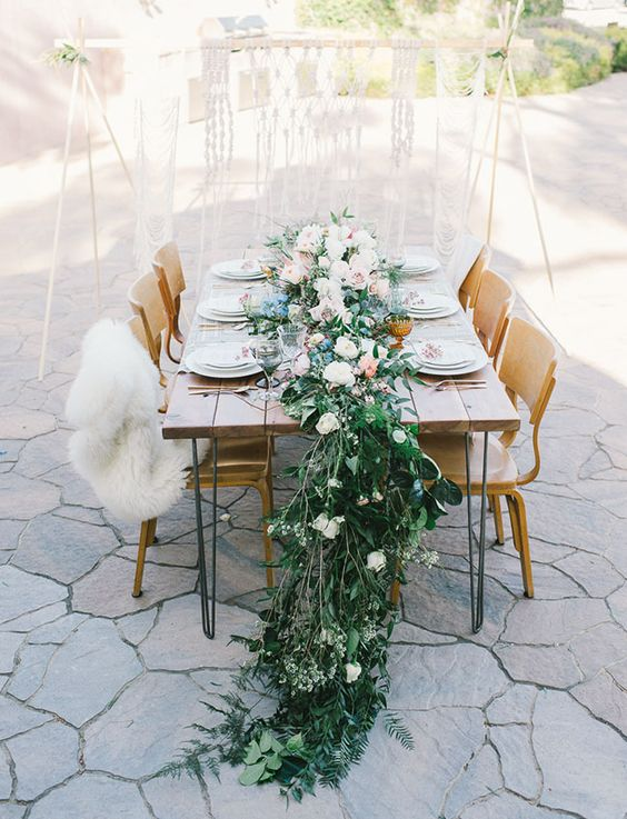 a fresh greenery and lush blooms table runner is enough, no centerpieces and tablecloths are needed