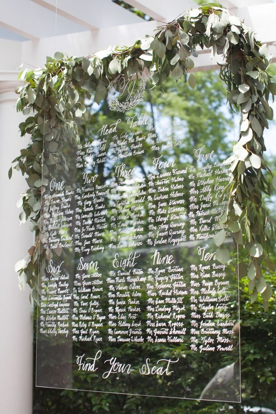 an acrylic seating chart hanging in the air and topped with a lush eucalyptus garland