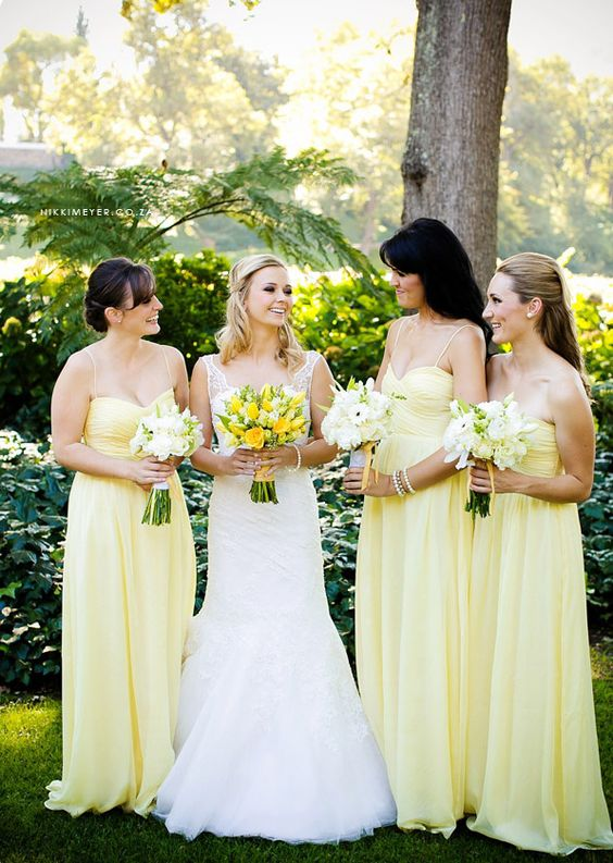 bridesmaids wearing light yellow spaghtti strap gowns and carrying white bouquets