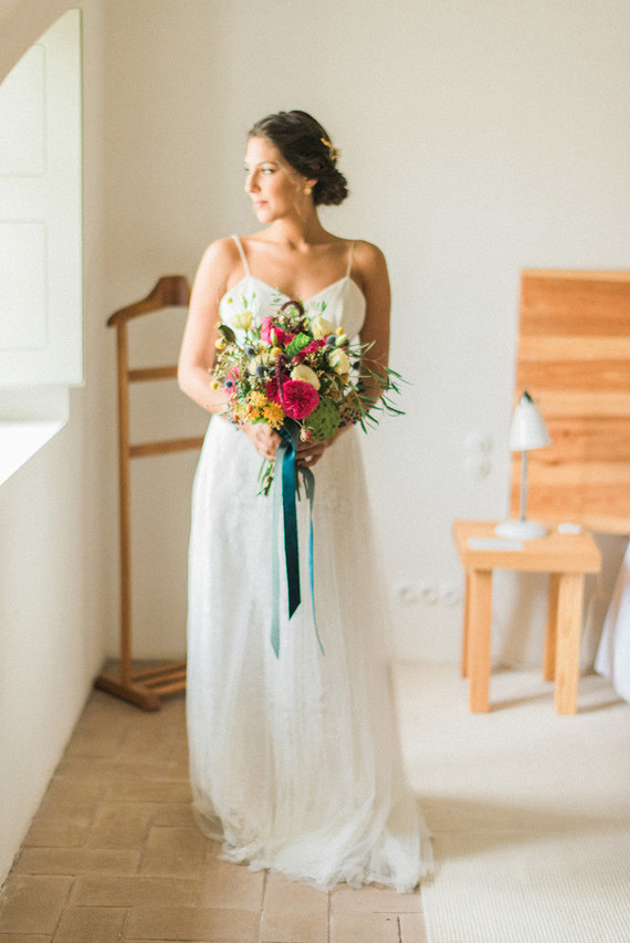 She was carrying a very bold and colorful wedding bouquet in the shades of yellow and pink with turquoise ribbons