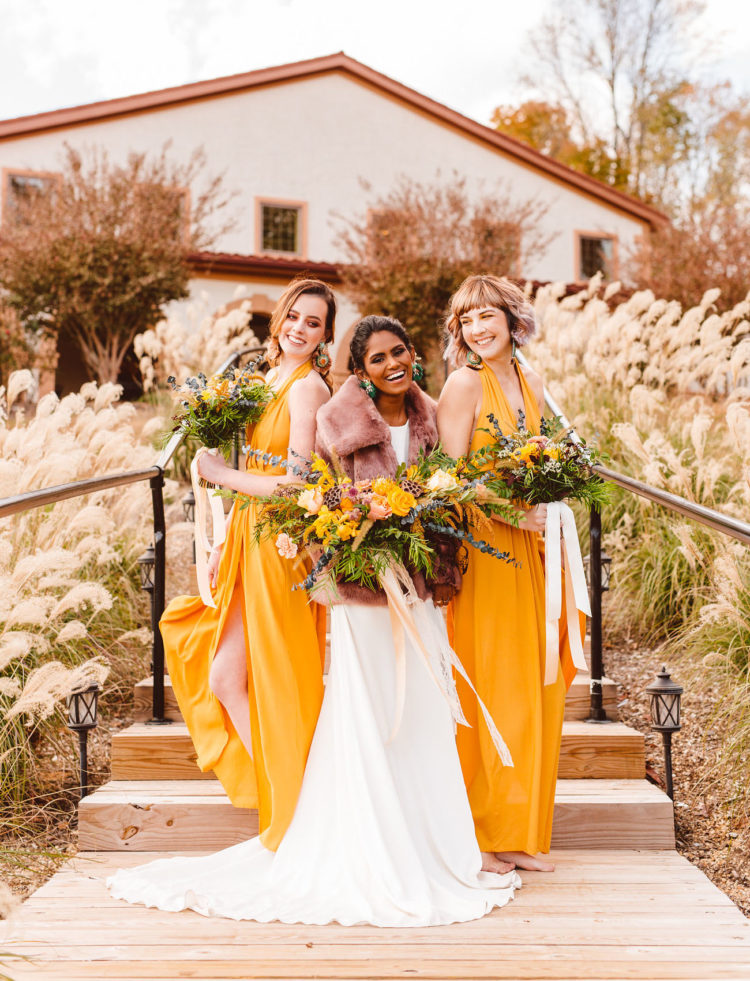 The bridesmaids were wearing chic mustard yellow maxi dresses with slits and statement earrings
