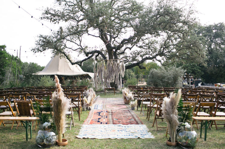 The ceremony space was done with pampas grass, boho rugs and fresh greenery, pampas grass is one of the trends
