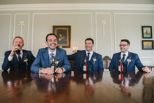 The groom and groomsmen were wearing three-piece blue suits and printed ties