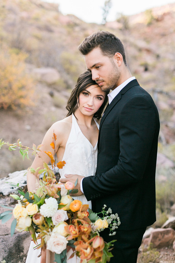 The groom was wearing a black suit and no tie plus brown boots for a relaxed boho look