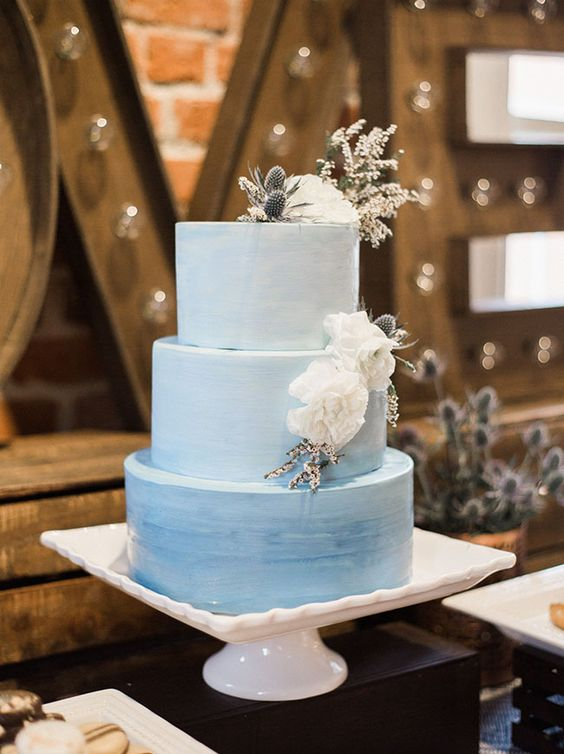 a blue watercolor ombre wedding cake topped with white blooms and thistles on top