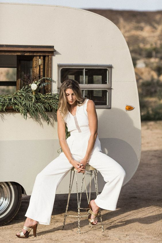 a bridal jumpsuit with a lace covered plunging neckline and wide pants brings an instant boho feel