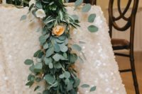 04 a lush greenery and subtle blooms table runner over a pearly sequin tablecloth