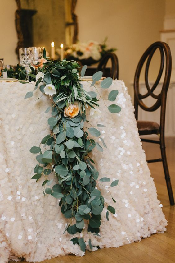 a lush greenery and subtle blooms table runner over a pearly sequin tablecloth
