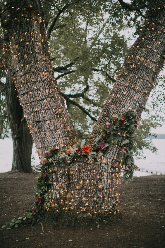 a tree covered with lights and with a greenery and floral garland for a wedding backdrop