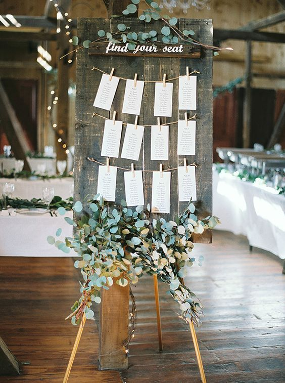 a weathered wooden board with a seating chart and lots of fresh eucalyptus to refresh the look
