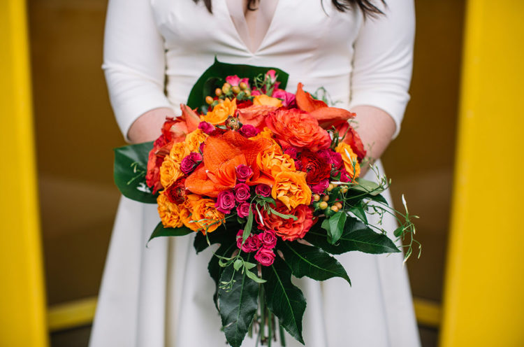 Her bouquet was packed with orange, red and fuchsia blooms plus tropical leaves
