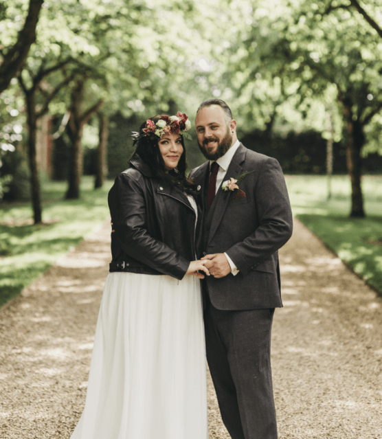 The bride covered up with a leather jacket and the groom was wearing a grey three-piece suit and a red tie