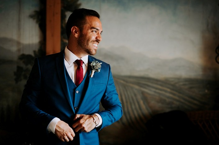 The groom was wearign a navy three-piece suit with a burgundy tie for a timelessly elegant look