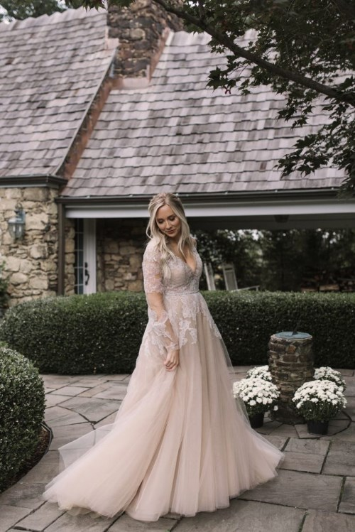 a blush wedding gown with white lace appliques, illusion sleeves and a deep V-neckline