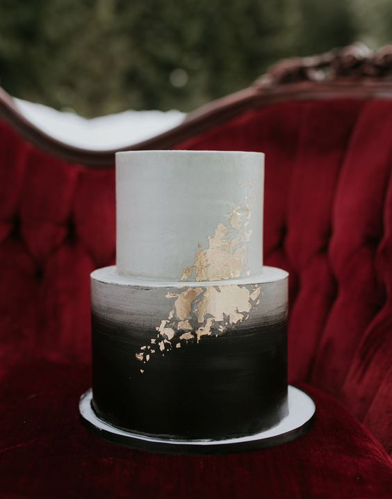 a brushed ombre black and white wedding cake with gold leaf decor for a bold wedding