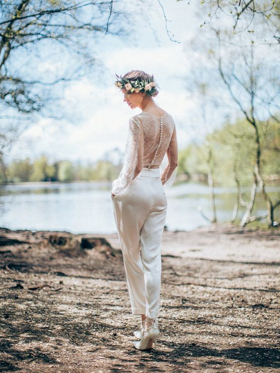 a chic bridal jumpsuit with a lace bodice on buttons and long sleeves and plain slik pants, high heels for a romantic feel