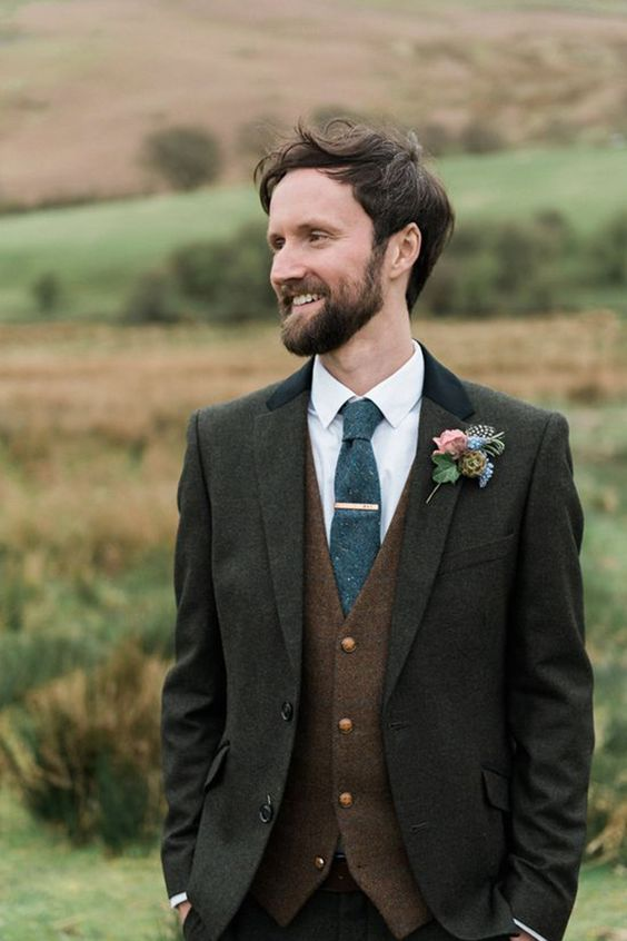 a dark grey three piece suit with a brown vest, a graphite grey tie and a floral boutonniere