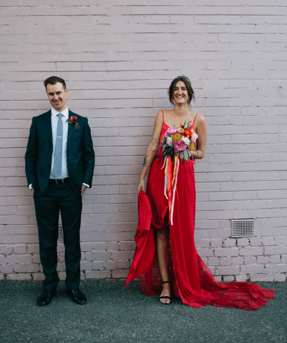 a fiery red spaghetti strap wedding dress with a front slit, an asymmetrical skirt and a train