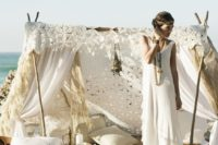 05 a gorgeous boho wedding teepee with lots of pillows and lanterns for a boho beach wedding