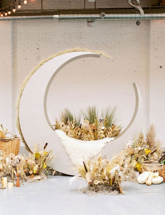 a gorgeous wedding altar with a crescent moon covered with pampas grass, herbs and leaves installations around it