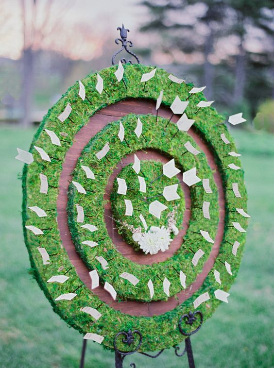 a moss circle seating chart with arrow escort cards and some blooms is a creative garden idea