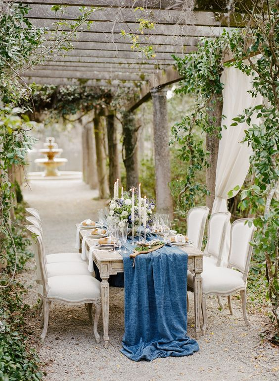 a refined reception space in the garden with climbing greenery and a blue table runner
