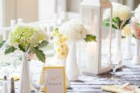 05 grey and yellow table decor with some floral centerpieces. a white lantern and colored napkins