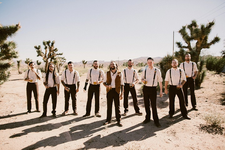 The groomsmen were wearing white shirts, brown pants and black suspenders