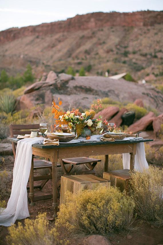 The wedding table setting was done with an airy table runner, with a lush fall inspired boho floral centerpiece