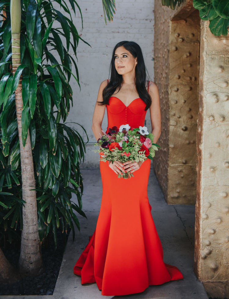 a fiery red mermaid wedding dress with a sweetheart neckline, buttons and a train for a catchy look