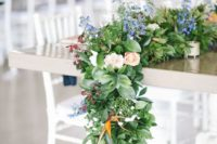 06 a lush greenery and pastel blooms table garland is a trendy way to style the tablescape