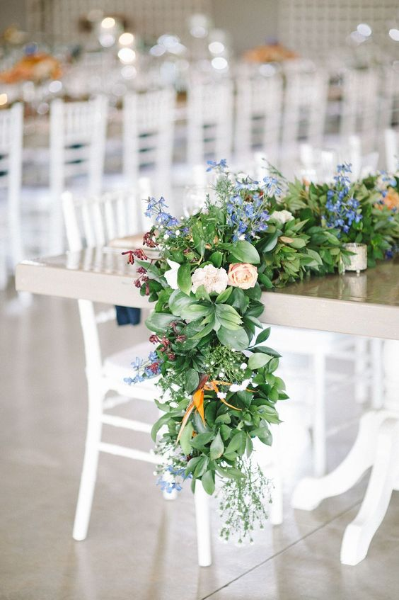 a lush greenery and pastel blooms table garland is a trendy way to style the tablescape
