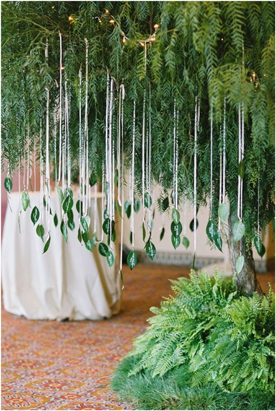a lush greenery decoration with leaf escort cards on long threads is a unique solution