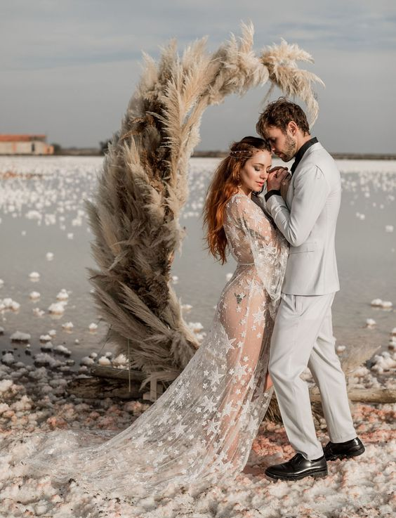 a pampas grass crescent moon wedding backdrop is gorgeous and will catch everybody's eyes