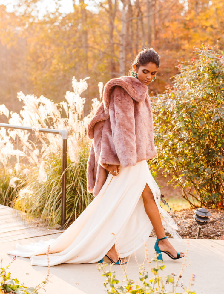The bride covered up with a mauve faux fur jacket to feel warm