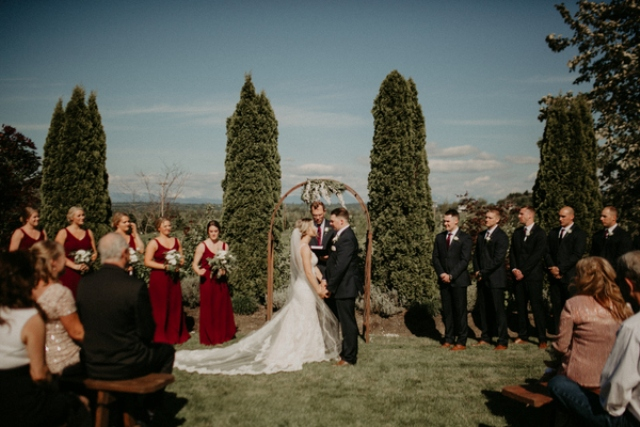 The bridesmaids were wearign burgundy maxi dresses, and the groomsmen were wearing black suits with burgundy ties